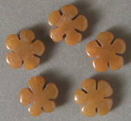 Five carved flower beads from yellow aventurine.