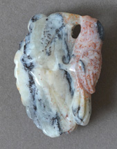 Yellow/white opal with red speckled bird carving.
