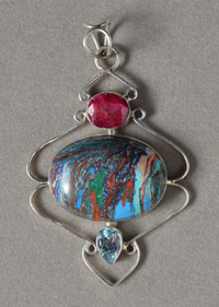 Rainbow calcite pendant with ruby and blue topaz accents.
