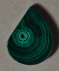 Malachite flat pendant bead in freeform drop shape.