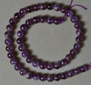 Strand of 8mm round beads from dark colored amethyst quartz.