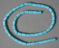 Blue turquoise drum beads with black lines.