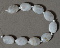 White Mexican agate flat oval beads.