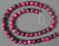Rhodonite round beads which have been dyed.