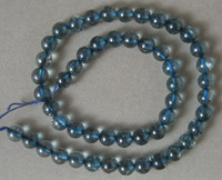 Strand of round beads from light blue tourmaline colored man made material.