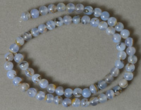 Round beads from blue chalcedony with inclusions.
