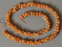Bone shaped beads from orange aventurine.