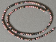 Small round beads from pink and black rhodonite.
