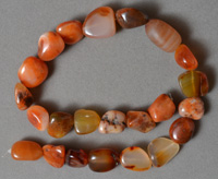 Mixed carnelian nugget beads on strand.