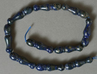 Lapis Lazuli beads carved in ornate bottle shape.